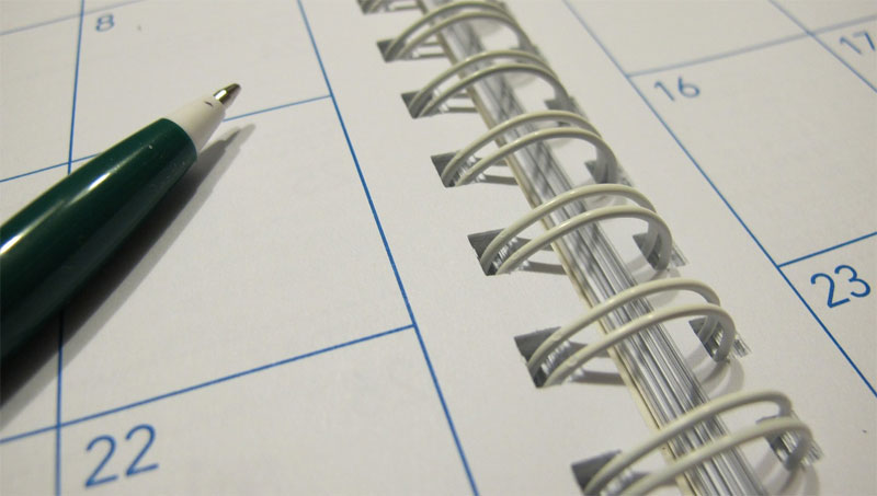 Blank calendar with pen resting on top