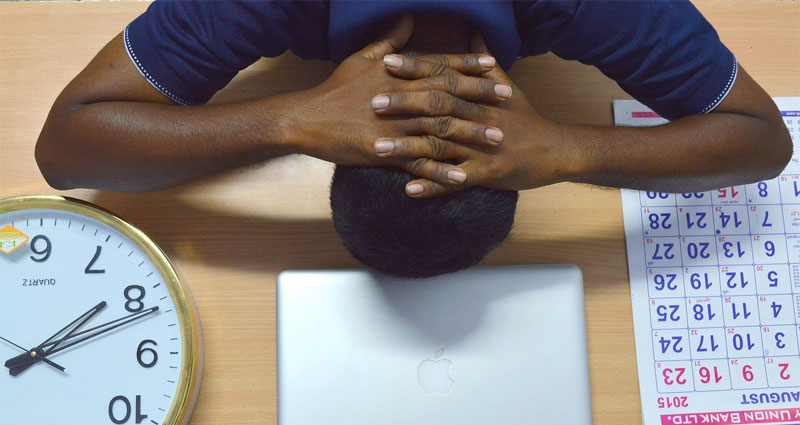 Stressed man with head on desk